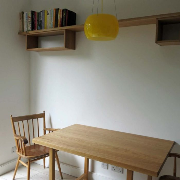 Simple kitchen table in oak with suspended shelving above